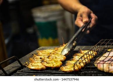 man fries prawns on the grill. Thai seafood