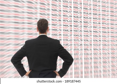 A Man in front of a big screen with numbers