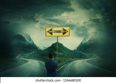 Man in front of a crossroad, fork junction and road sign arrows splitted in two different ways. Go back in 2018 or move to 2019 year. Choosing correct pathway. Live in the past or change your life.