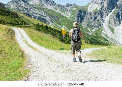 Man in front of crossroads in the mountains, Austria