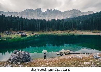 Man in front of Lago Di Carezza with Latemar mountain range, Dol