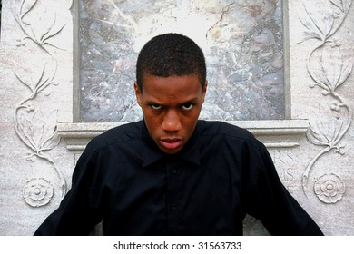 Man in front of marble looking mean