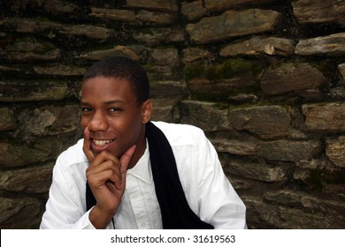 A man in front of mossy wall smiling