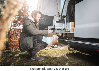Man in front of a van using a build in camping stove