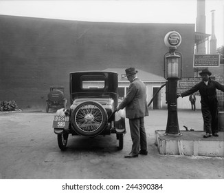 Man fueling his car at a self-service Standard Motor gas station in Washington D.C. area. A sign tells customers the gasoline is filter and contains no dirt or water. 1920.