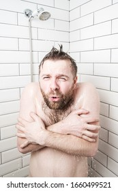 Man, with a funny expression on his face, feels shocked at taking a cold shower, he froze and tries to cover his body with hands.