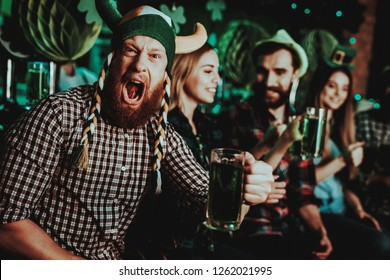 Man In Funny Hat Celebrates St Patrick's Day. Bar Counter. Alcohol Handling. Ginger Beard. Smiling Male. Good Festive Mood. Bright Lights. Funny Club Visitor. Open Mouth. Glass Of Beer.