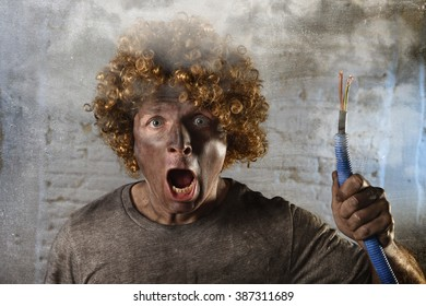 man with funny wig holding electrical cable smoking after domestic accident with dirty burnt face and shock electrocuted expression in electricity DIY repairs danger concept in black smoke background