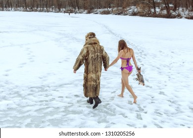 Man in a fur coat and a girl in a bathing suit go hand in hand on the frozen lake.