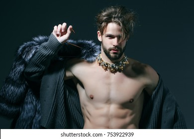 Man with fur coat on grey background. Cinderella prince with crown and muscular torso, chest. Freak, gay and transvestite. Drag queen, homosexual and trans. Winter fashion, jewelry, accessory.