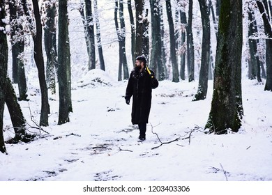 Man in fur coat walking in forest with axe on shoulder. lumberjack concept. lumberjack man working in the winter forest. Guy near trees covered by snow on background. Brutal woodsman concept.