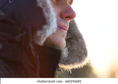 Man with a fur hat outside in cold winter temperature close up