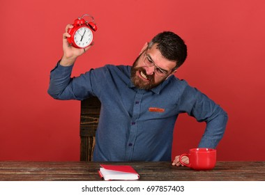 Man with furious face sits at wooden table. Deadline and bad job concept. Worker with beard and glasses tries to break alarm clock, red background. Cup, retro clock and red book on vintage desk