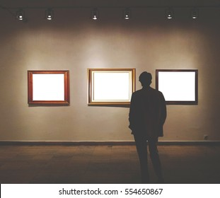 Man in gallery room looking at empty picture frames - Mock up art concept