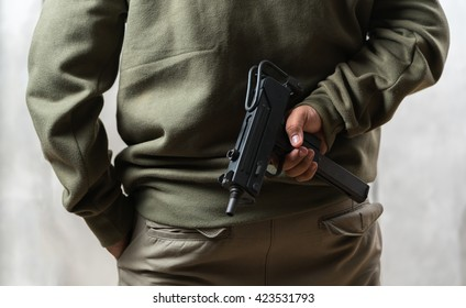 A man,  gangster concealing his gun behind his back