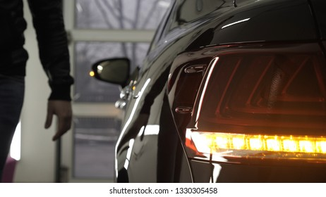 A man in the garage (car service) Checks the car alarm and then goes off (comes in) turning off (turning on) the lights behind him. Concept of: Auto garage, Security.