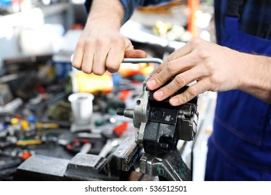 The man in the garage with a wire brush cleans mechanical parts