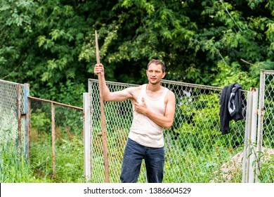 Man in garden cutting weeds oat grass with sickle scythe manual tool in green summer in Ukraine dacha or farm farmer hot scratching armpit