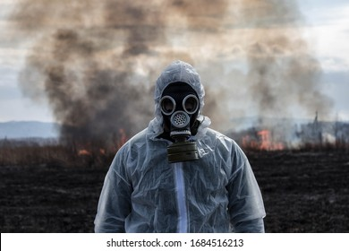 A man in a gas mask in a chemical protective suit shrouded in smoke is walking in a dangerous radioactive zone. A Stalker soldier. Post-Apocalypse. Nuclear war. Environmental disaster.