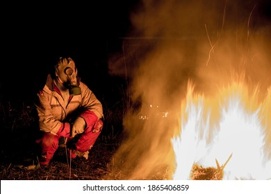 a man in a gas mask in a poor environment after a pandemic at night near the fire