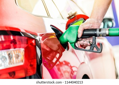 Man at gas Station refueling gasoline or diesel. Hand with clear gloves holding fuel pump or pistol.