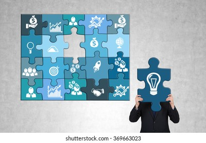 man gathering a blue business puzzle with business icons on each part. The man holding the last 'bulb' part missing so that he hides head behind it. Greyish background. Concept of doing business.