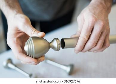 A man gathers metal cornices. Close up