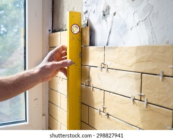 Man with gauge measuring  vertical linearity of installation ceramic tiles during renovation