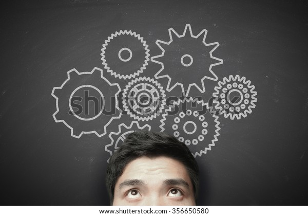 Man with gears on the blackboard background.