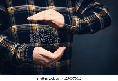 man with gearwheel mechanism design between his hands, with flannel shiirt and dark background