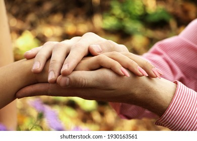 The man gently holds the hands of the girl on the background of the forest