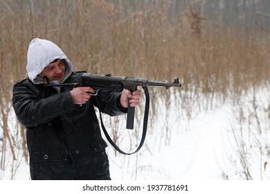 Man with German machine gun in winter forest