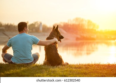 man and German Shepherd Dog,in nature watching sunset by the river