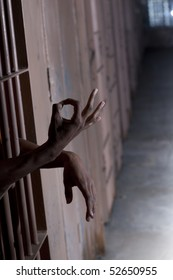 A man gestures the OK sign while sticking his hands through the bars of his prison cell. Vertical shot.