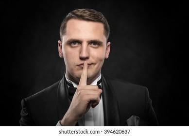 Man gesturing silent on a dark background.