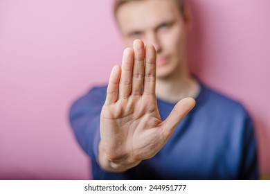 Man gesturing stop isolated on a yellow background