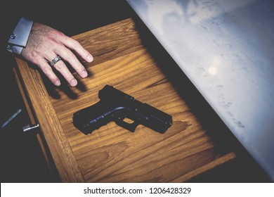 The man gesturing took a handgun that was placed in the desk drawer for some purpose.