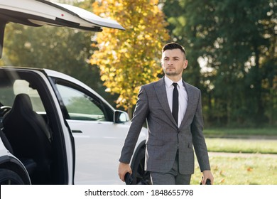 The man gets out of the car. Man in a strict business suit opens the door and gets out of a luxury car.