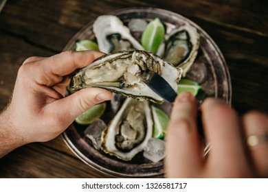a man gets an oyster from a shell.oyster  plate with lime and ice on the background