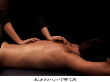 Man getting a back massage at spa, low key lighting with black background