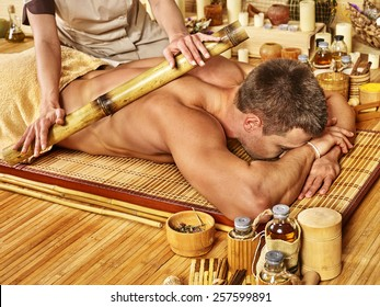 Man getting bamboo massage. Female hand  therapist.Wooden floor.