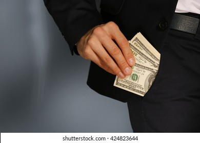Man getting dollar banknotes out of suit pocket on grey background