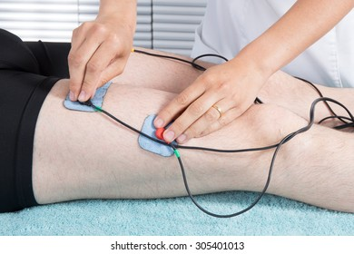 Man getting electric massage for leg muscles in spa