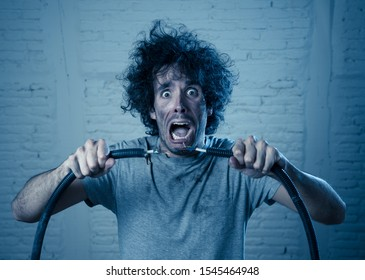 Man getting electric shock connecting broken electrical cables at home. Husband having domestic accident being electrocuted with dirty burnt face and crazy expression. Electricity DIY repairs danger.