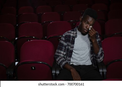 Man getting emotional while watching movie in theatre