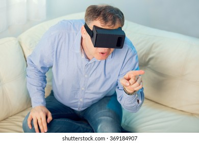 4f5454d87a0 Man getting experience using VR-headset glasses of virtual reality at home  much gesticulating hands