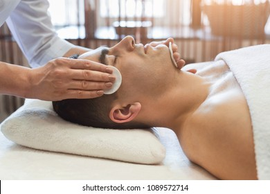 Man getting facial treatment in a beauty SPA salon. Exfoliation, stimulation and hydratation. Aesthetic cosmetology, closeup, copy space