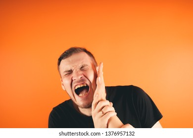 Man getting slapped on orange background. Unhappy scared man getting slapped standing on orange background