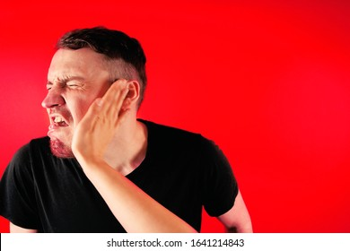 Man getting slapped on red background. Unhappy scared man getting slapped standing on red background