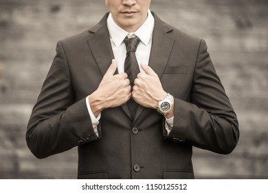Man getting suited up. Confident gentleman posing in suit and tie.